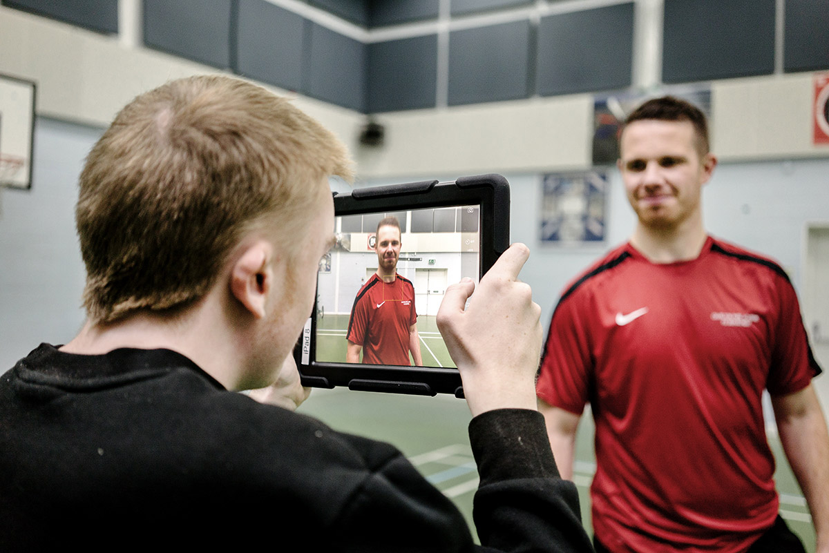 Using a touchscreen tablet to photograph a fellow student